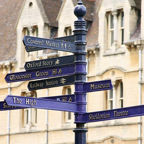 """""""Blue street sign in Oxford, England with many directions in front of classing Oxford architecture."""""""