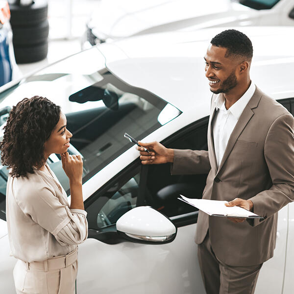 A woman is stood next to a new car talking to a car salesman