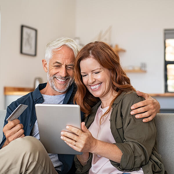 Middle-aged couple using iPad to shop online