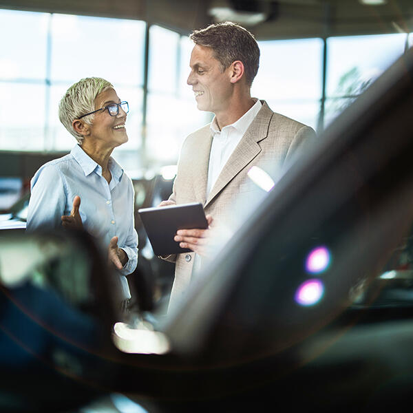 Senior car salesman and saleswoman happy at report on their tablet device