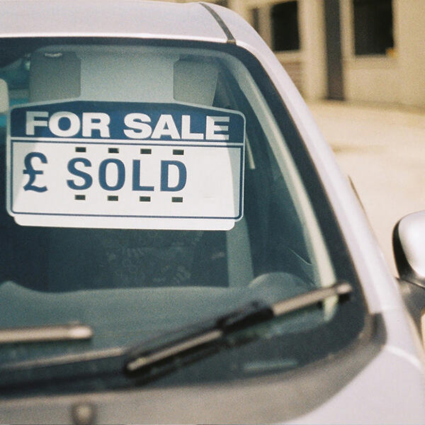 """Picture of a car with a sign in the window saying """"sold"""""""