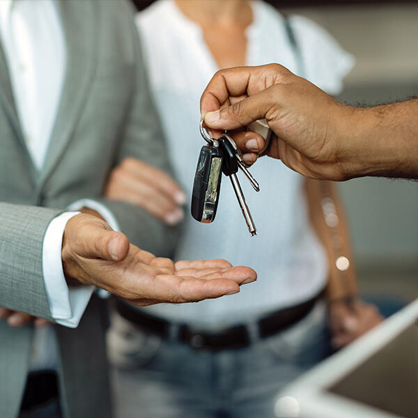 Close up of a sales man's hand giving keys to a car buyer