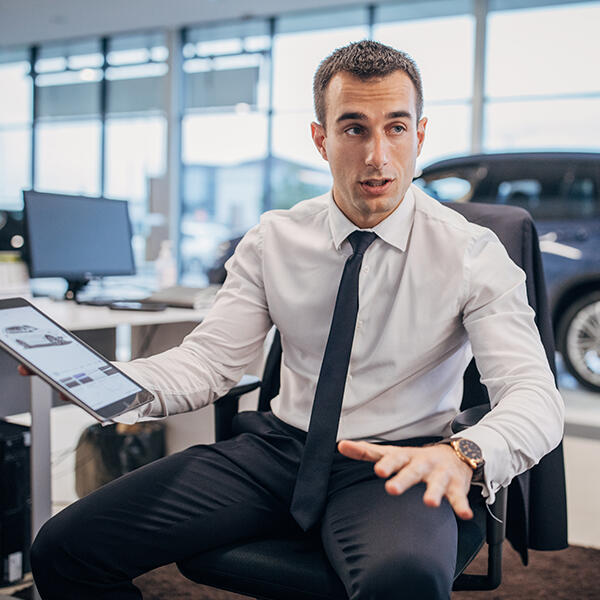Young salesman in shirt and tie holds a tablet device in his hand. The tablet screen shows a car sales website